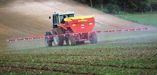 Farm vehicle spreading fertiliser to crops